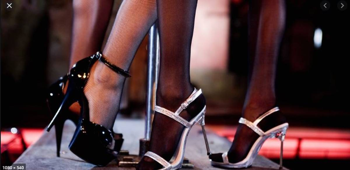 stripper heals on stage with pole